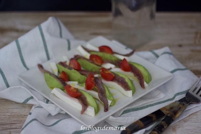 Aperitivo de aguacate, queso tierno, anchoas y cherrys
