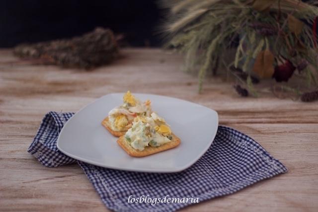 Aperitivo de ensaladilla sobre galletas saladas
