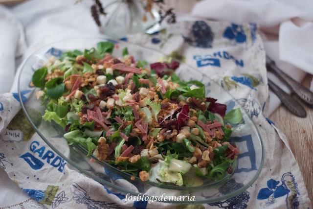 Ensalada con bacon, dados de queso, pan frito, frutos secos y vinagreta dulce