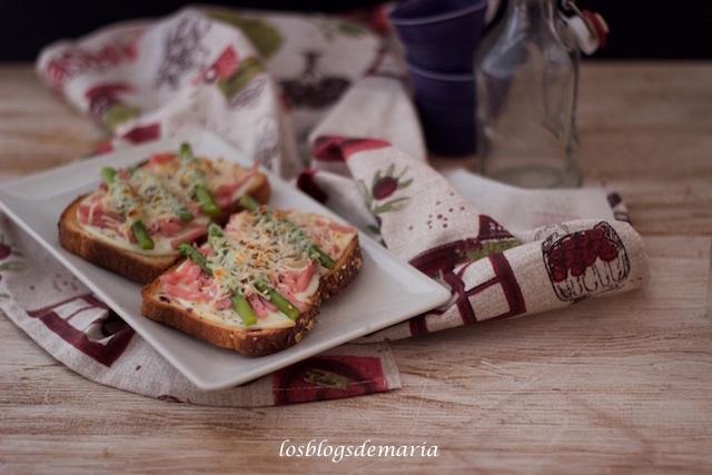 Tostas de pan de cereales, semillas y frutos rojos con jamón y espárragos