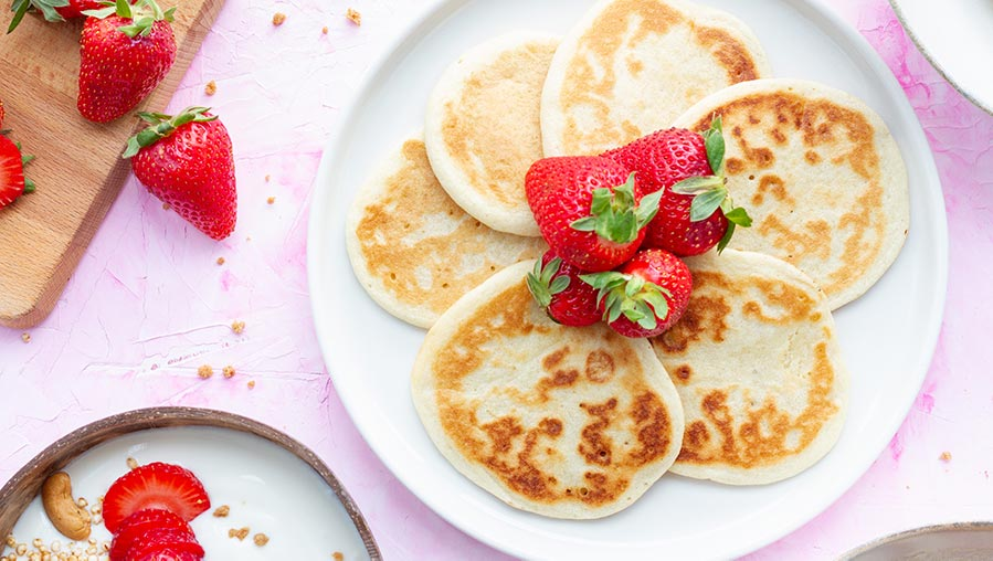 Desayuno saludable de tortitas esponjosas, bol de yogur y fresas